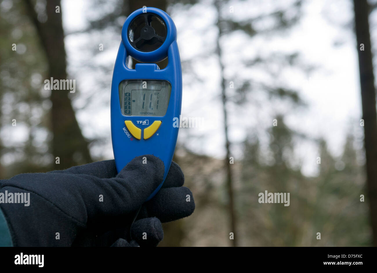 Gloved hand holding up a wind anemometer showing wind chill factor on cold day, UK - Stock Image