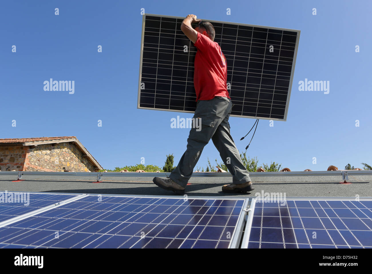Torre Alfina, Italy, man carries a solar collector on the roof of a detached house - Stock Image