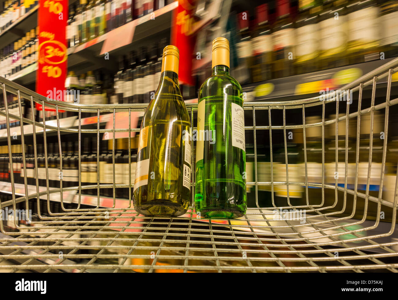 Bottles of wine in shopping trolley with 3 for 10 pound sing in background. Asda supermarket, England, UK - Stock Image