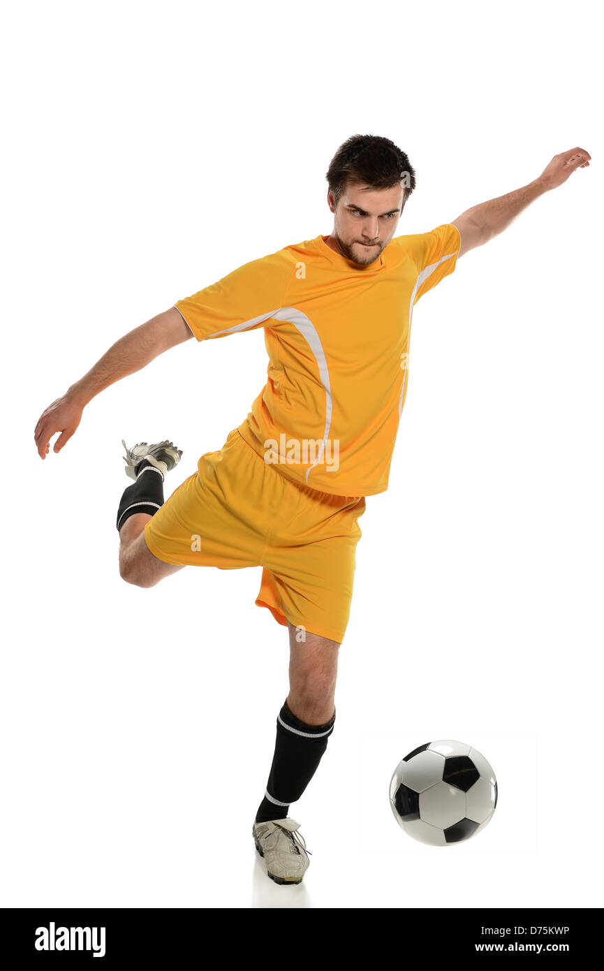 Young soccer player kicking ball isolated over white background - Stock Image
