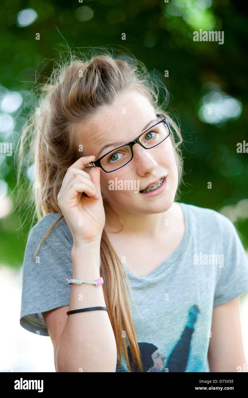 14507b6fc4e1 13-year-old teenage girl wearing glasses and dental braces. - Stock Image