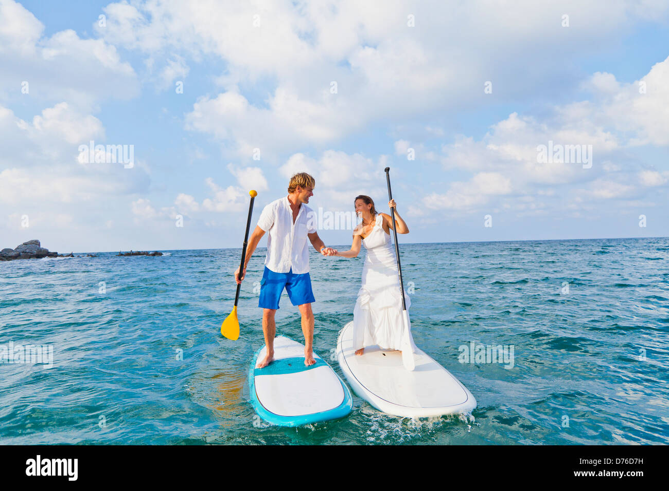 Dressed up mad and woman riding paddle boards Stock Photo