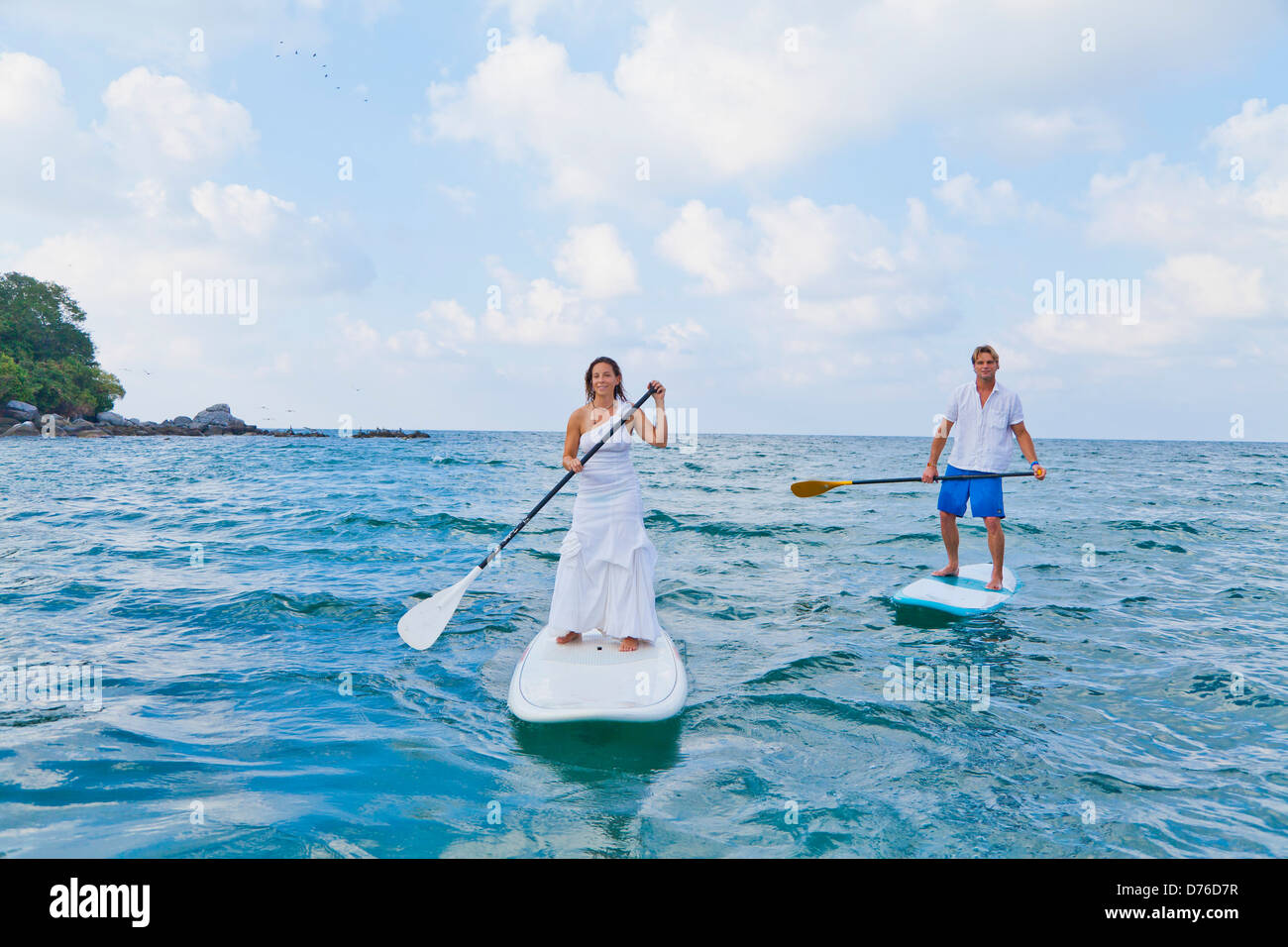Dressed up man and woman riding paddle boards Stock Photo