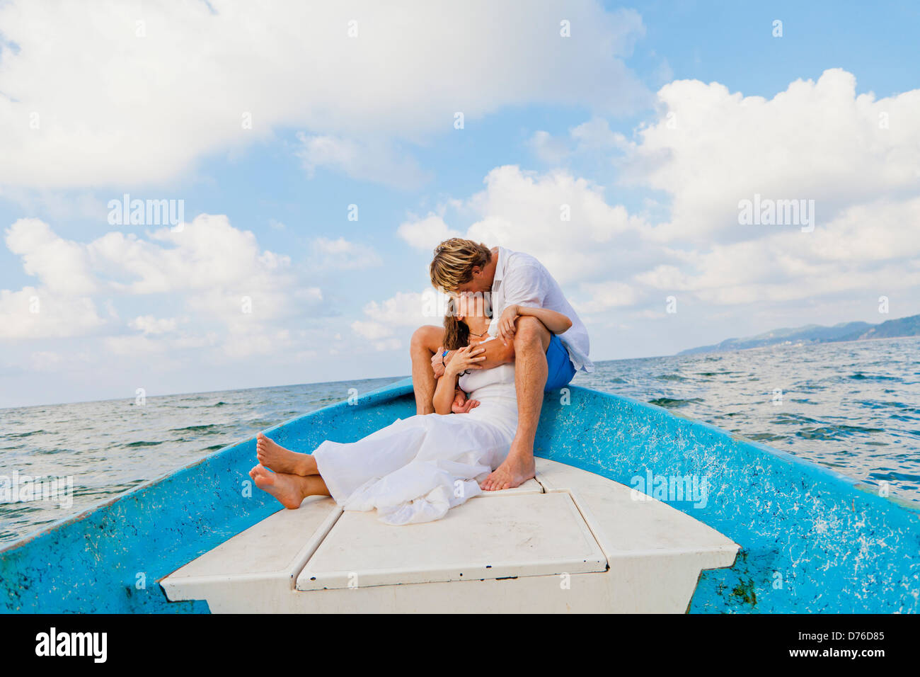 Man and woman embracing in bow of boat Stock Photo