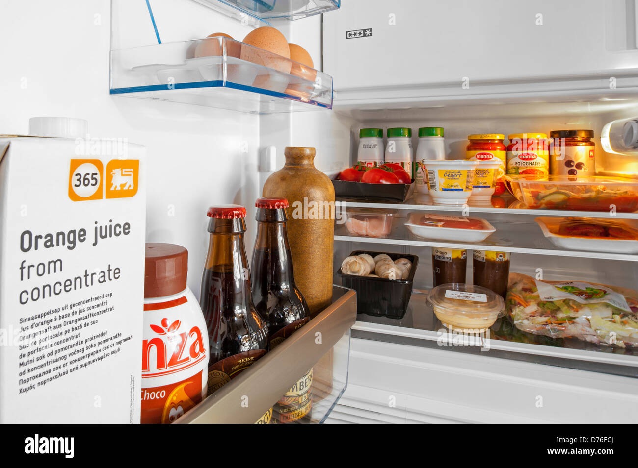 Cooled food and beverages in open fridge / refrigerator in kitchen - Stock Image
