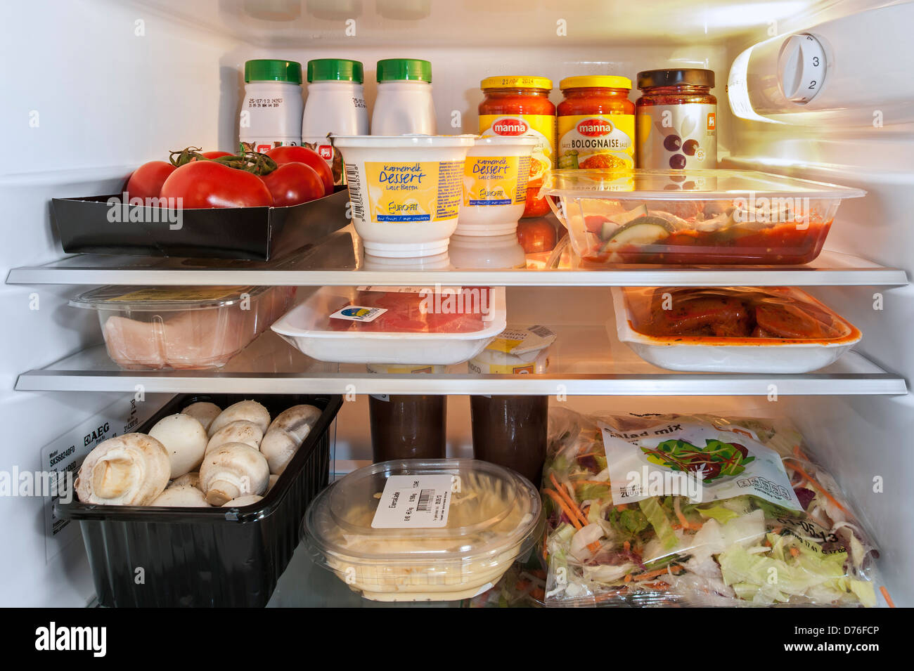 Cooled food in open fridge / refrigerator in kitchen - Stock Image