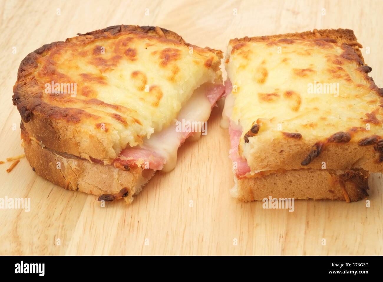 A toasted and cut open Croque Monsieur sandwich with melted cheese and ham - Stock Image
