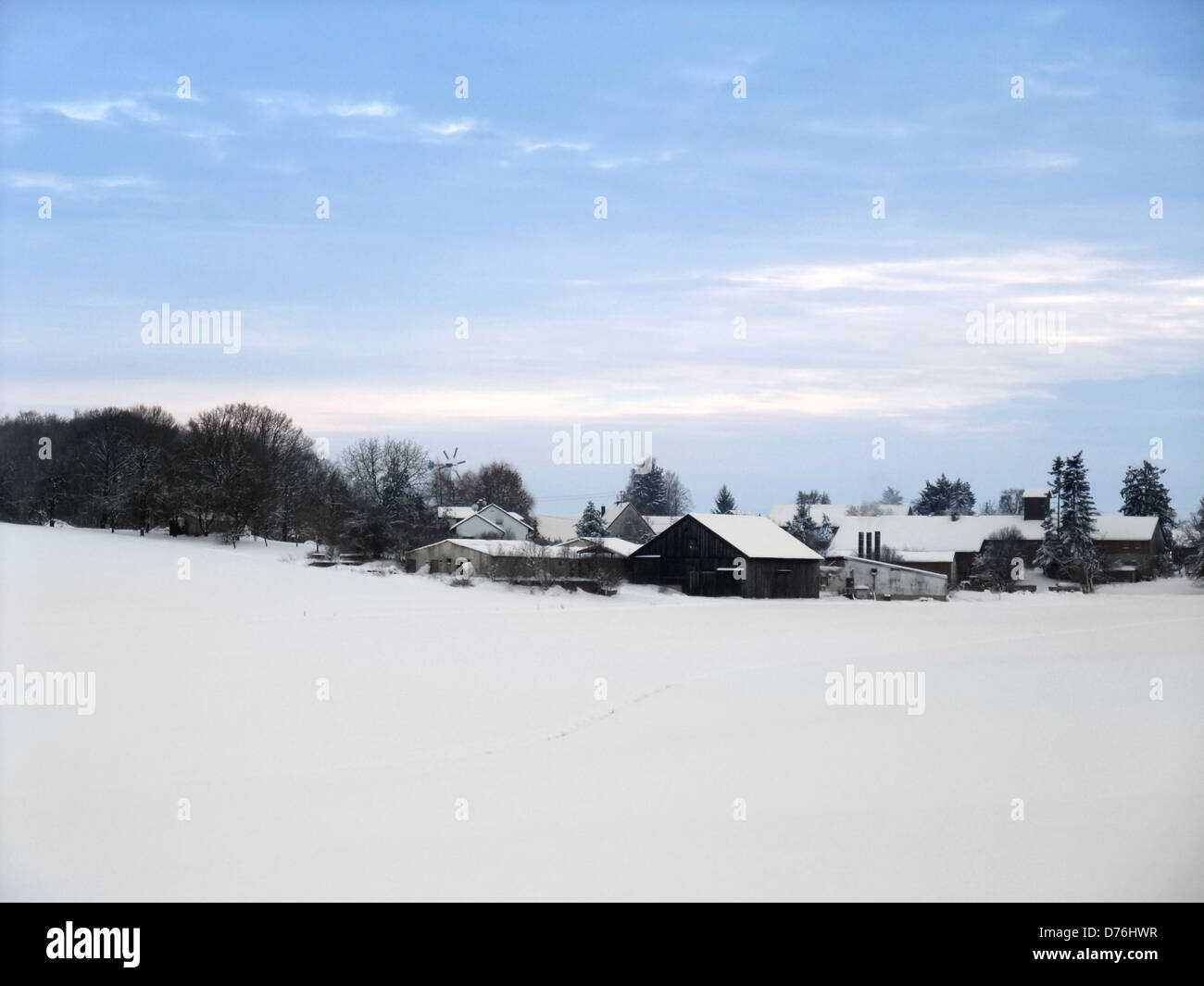 idyllic rural winter scenery with small village at evening time in Hohenlohe, an area in Southern Germany Stock Photo