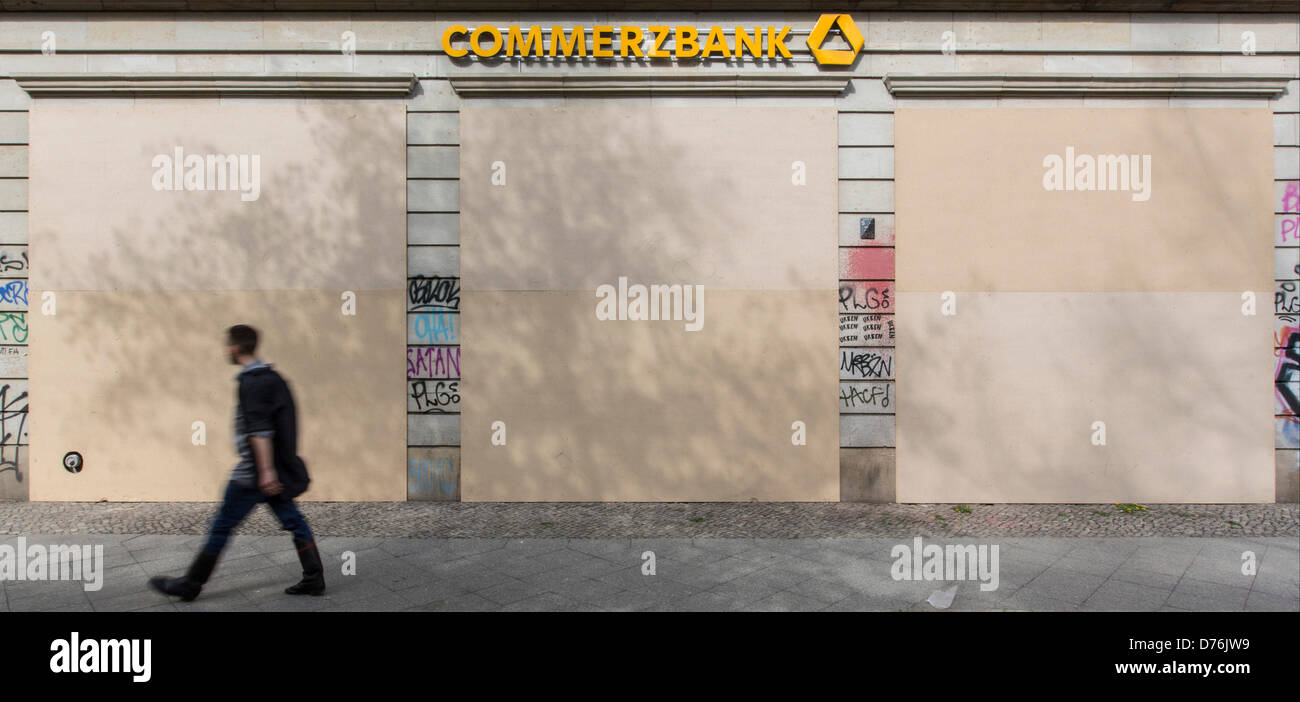 Berlin, Germany, 30 April 2013. Young man walks past a protected bank in Friedrichshain in Berlin. A row of demonstrations - Stock Image