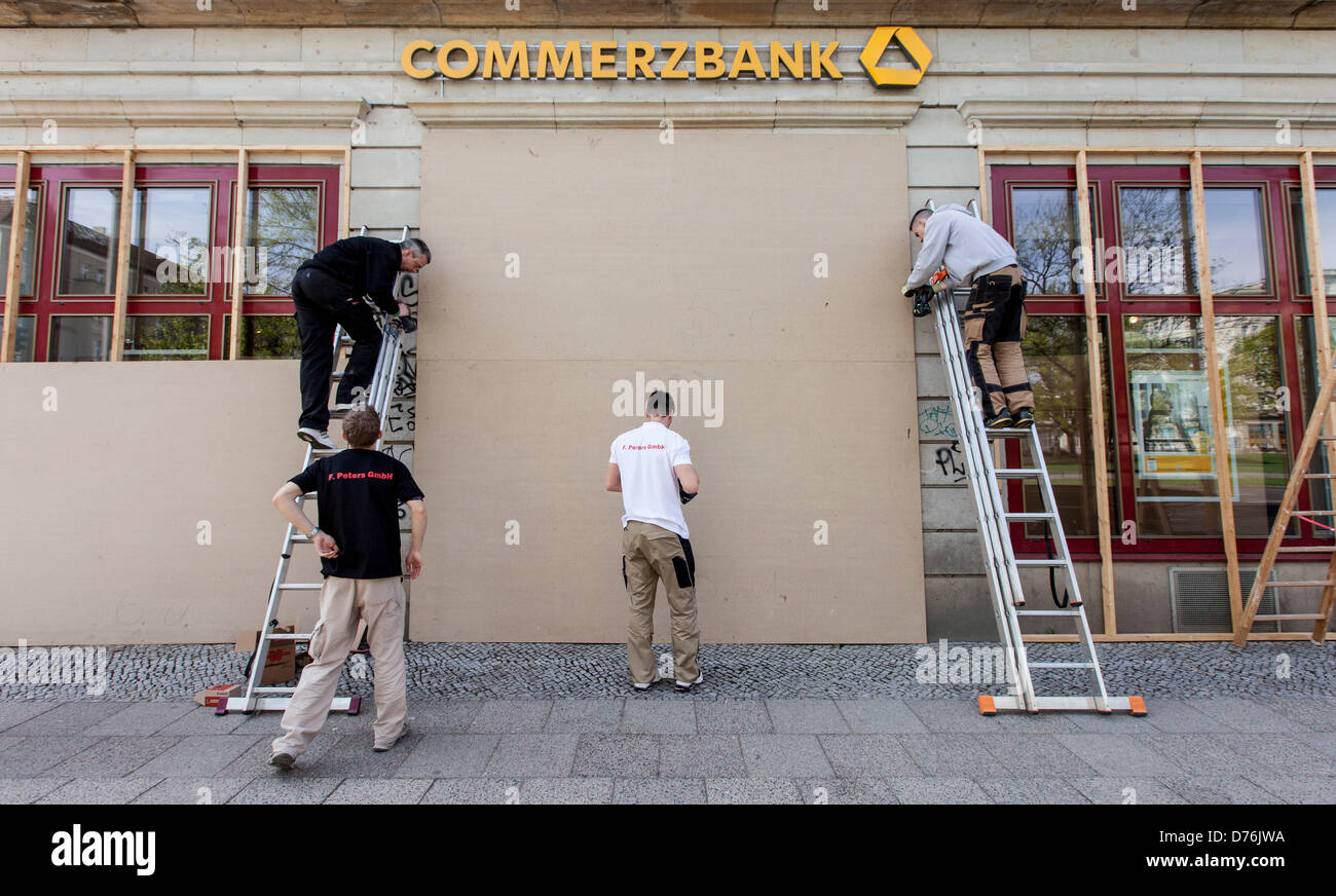 Berlin, Germany, 30 April 2013. Employees from a craft company put particle boards over a bank in Friedrichshain - Stock Image