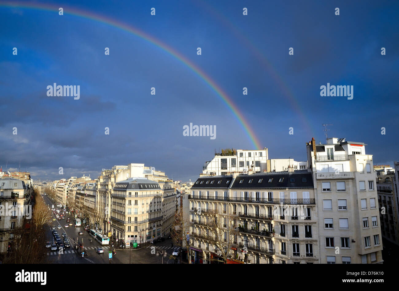 Boulevard Haussmann  skyline with rainbow against dark blue sky Paris France EU - Stock Image