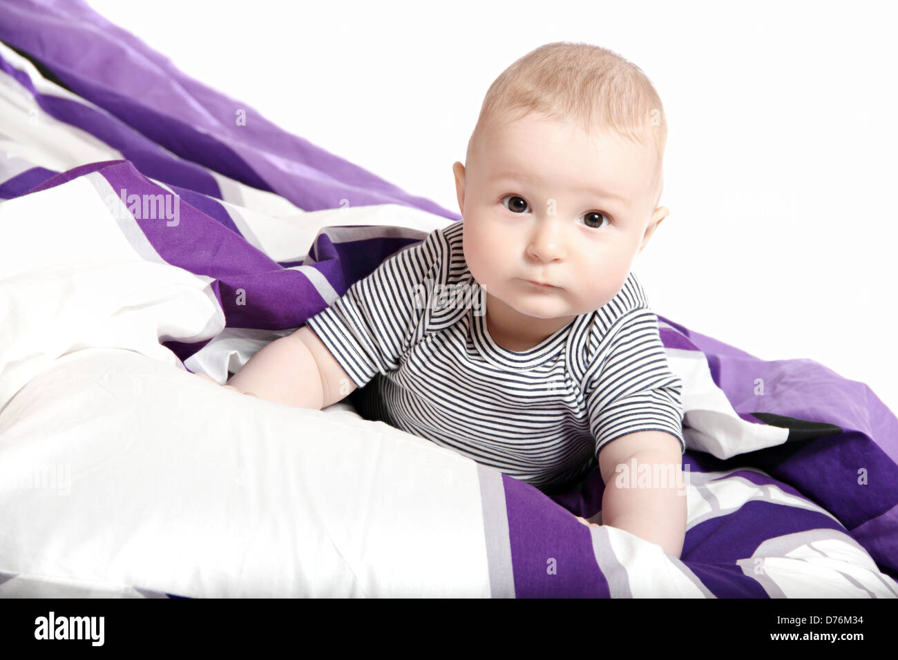Toddler on bed under blanket - Stock Image