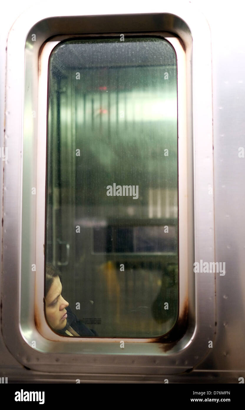 A commuter sleeps against the window of a New York City subway train. Stock Photo