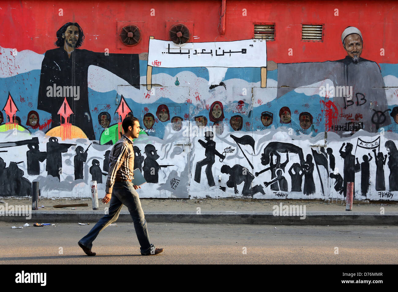 Man walks in front of a revolutionary mural on a wall of martyrs near Tahrir Square in Cairo. - Stock Image
