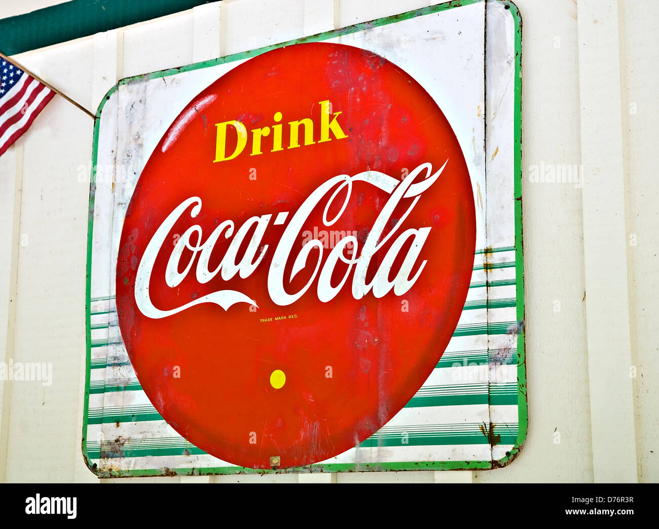 An old metal Coca-Cola sign on the side of a building. - Stock Image