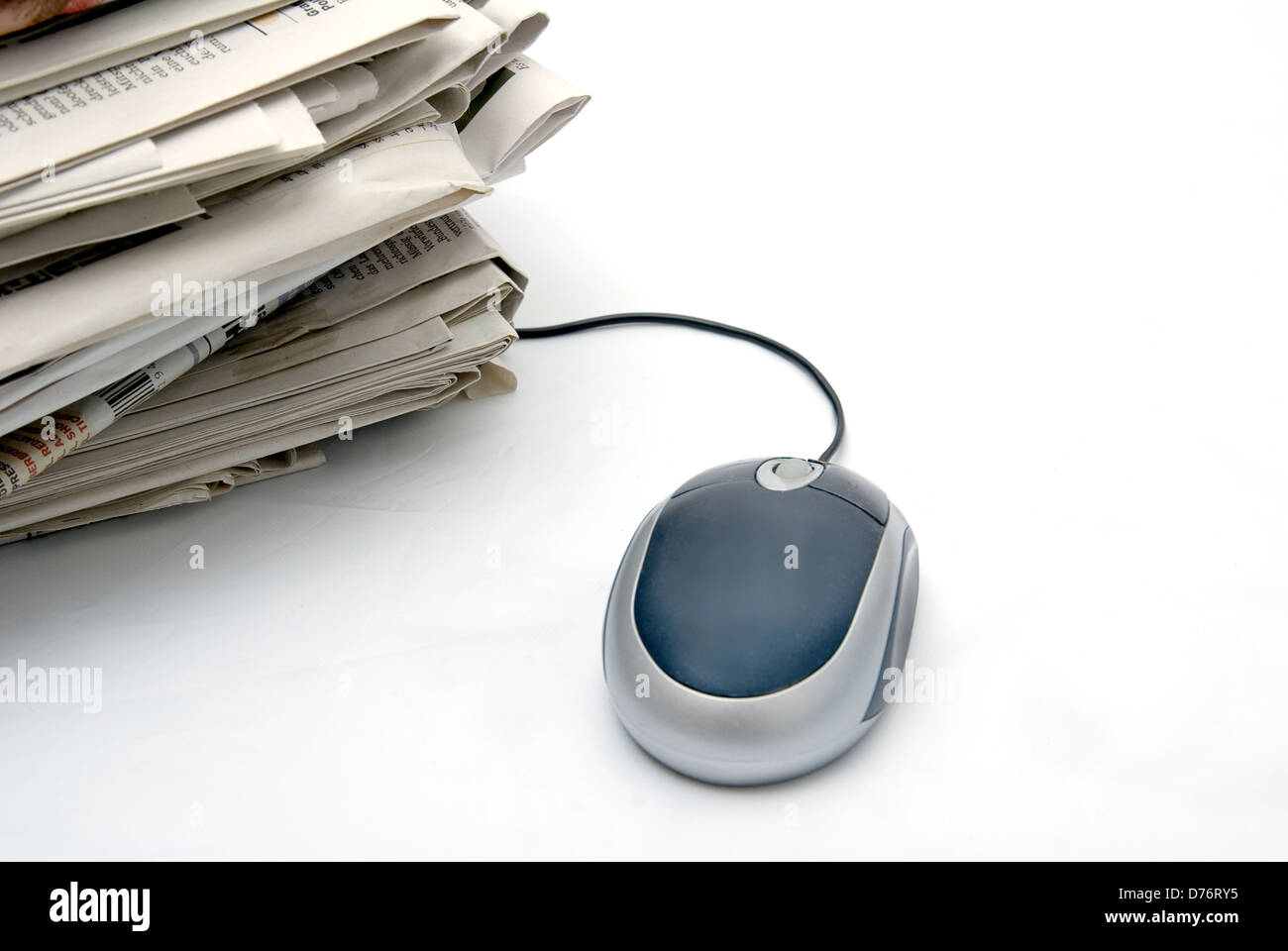 pc mouse next to a pack of classic newspapers on light background with copy space Stock Photo