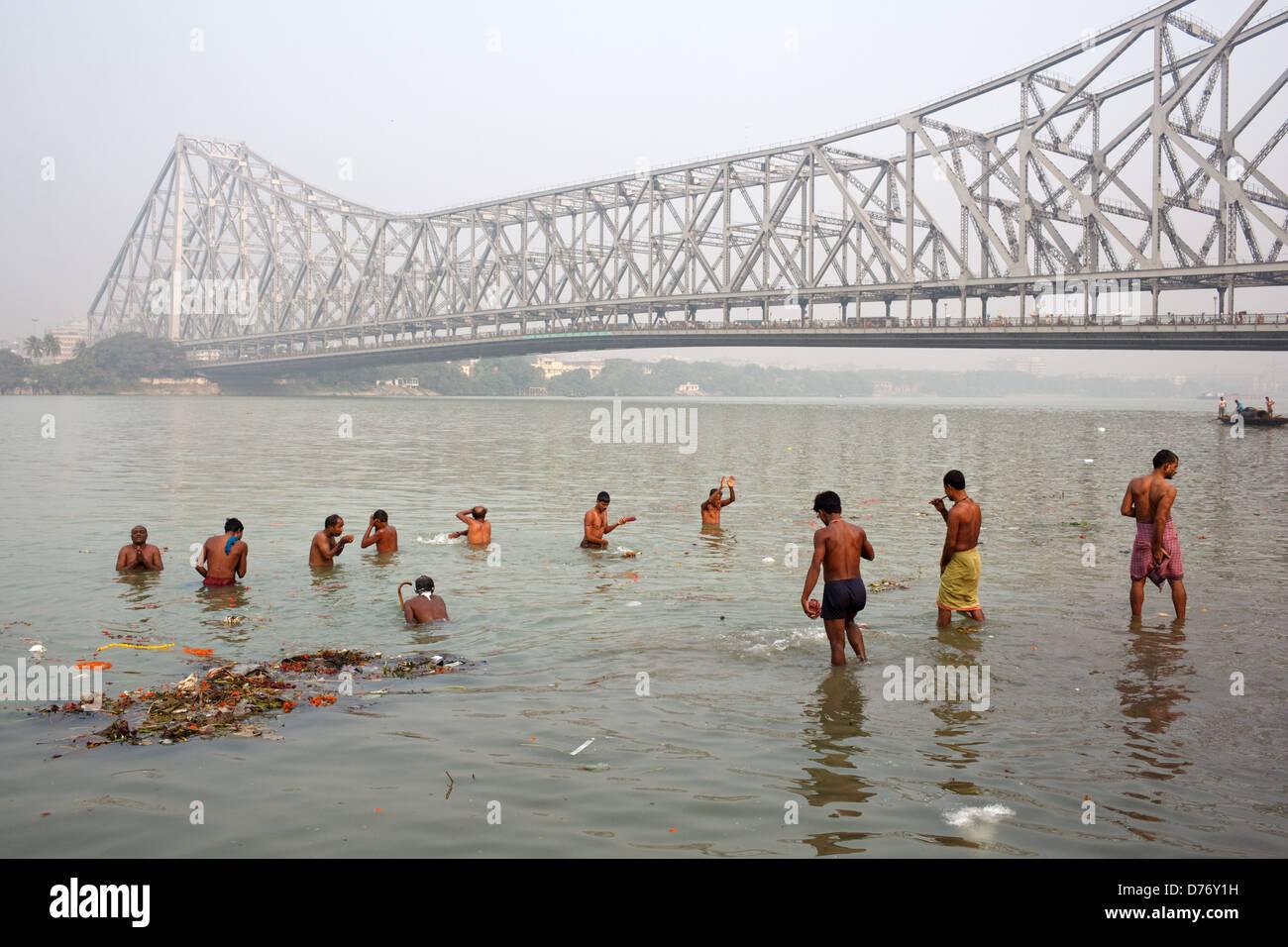 People take morning bath in Hooghly River near Howrah Bridge (Rabindra Setu) in Kolkata, India. - Stock Image