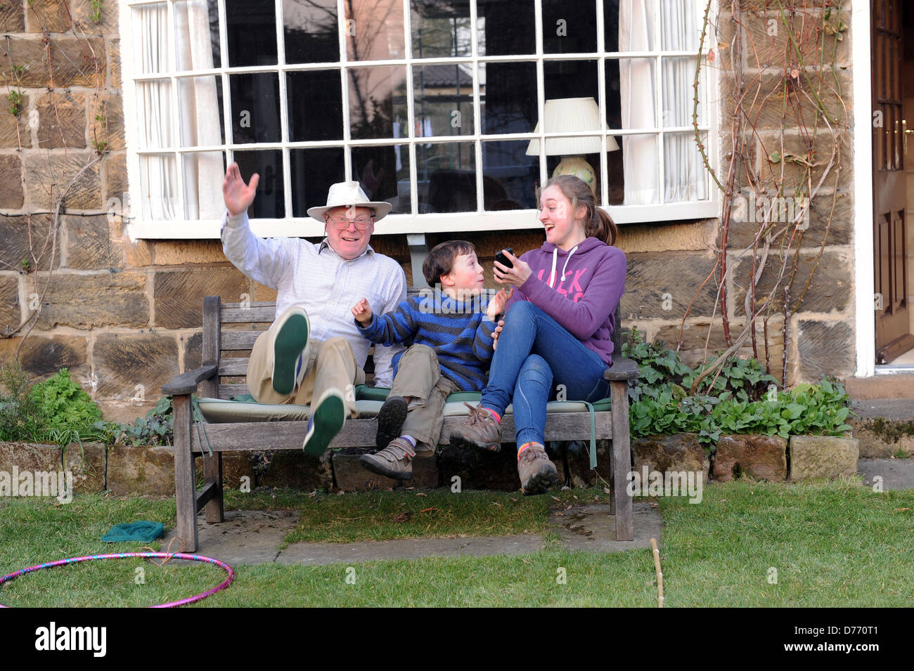 grandfather and grandchildren celebrating the grandfather's speedy time in a garden obstacle competition - Stock Image