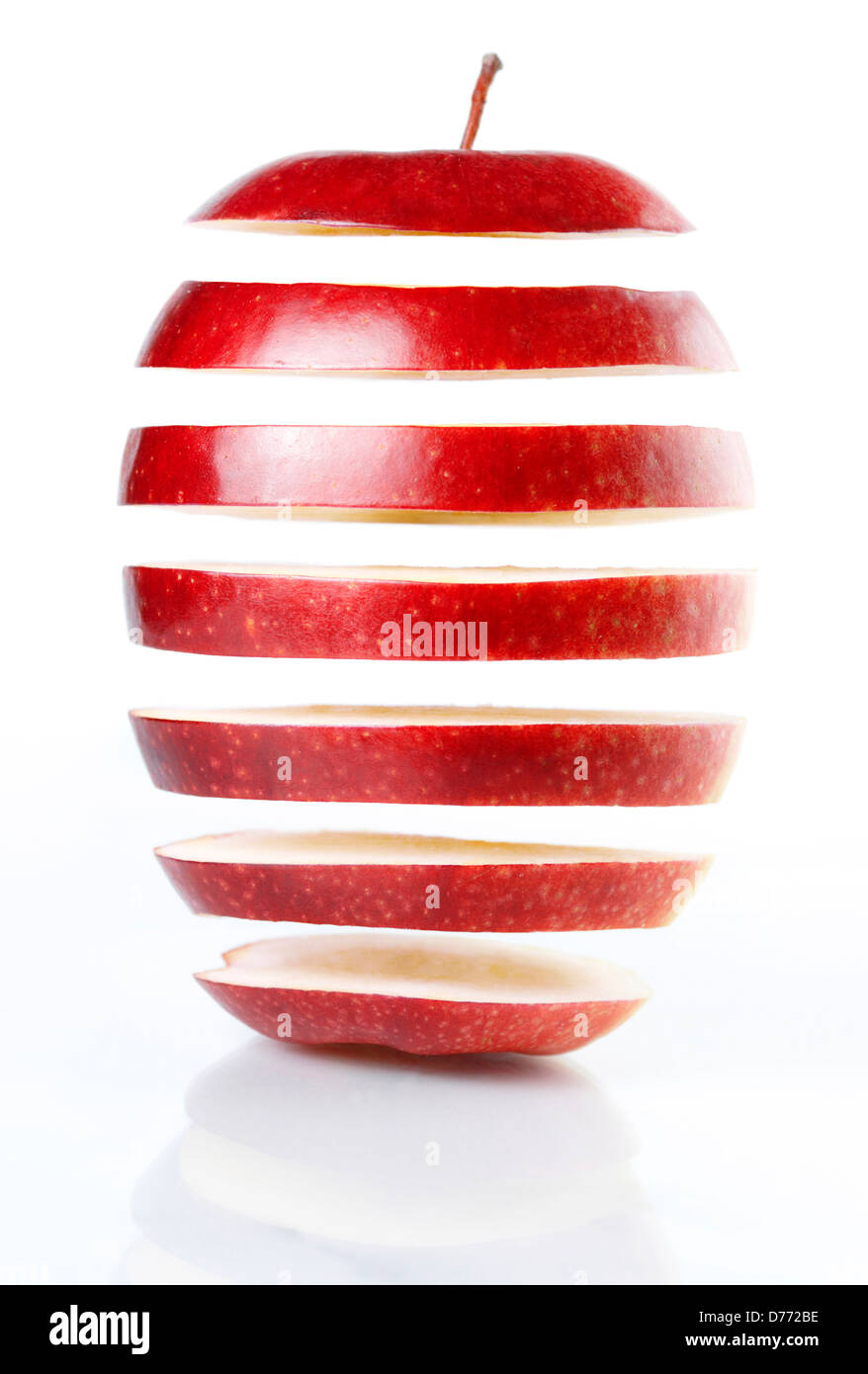 Slices of red apple hanging in mid-air isolated on white background. Food genetical engineering concept. - Stock Image