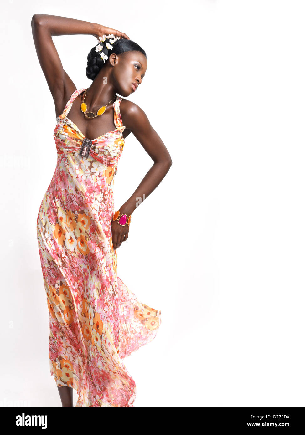 Beautiful young african american woman wearing a flying pink floral summer dress isolated on white background - Stock Image