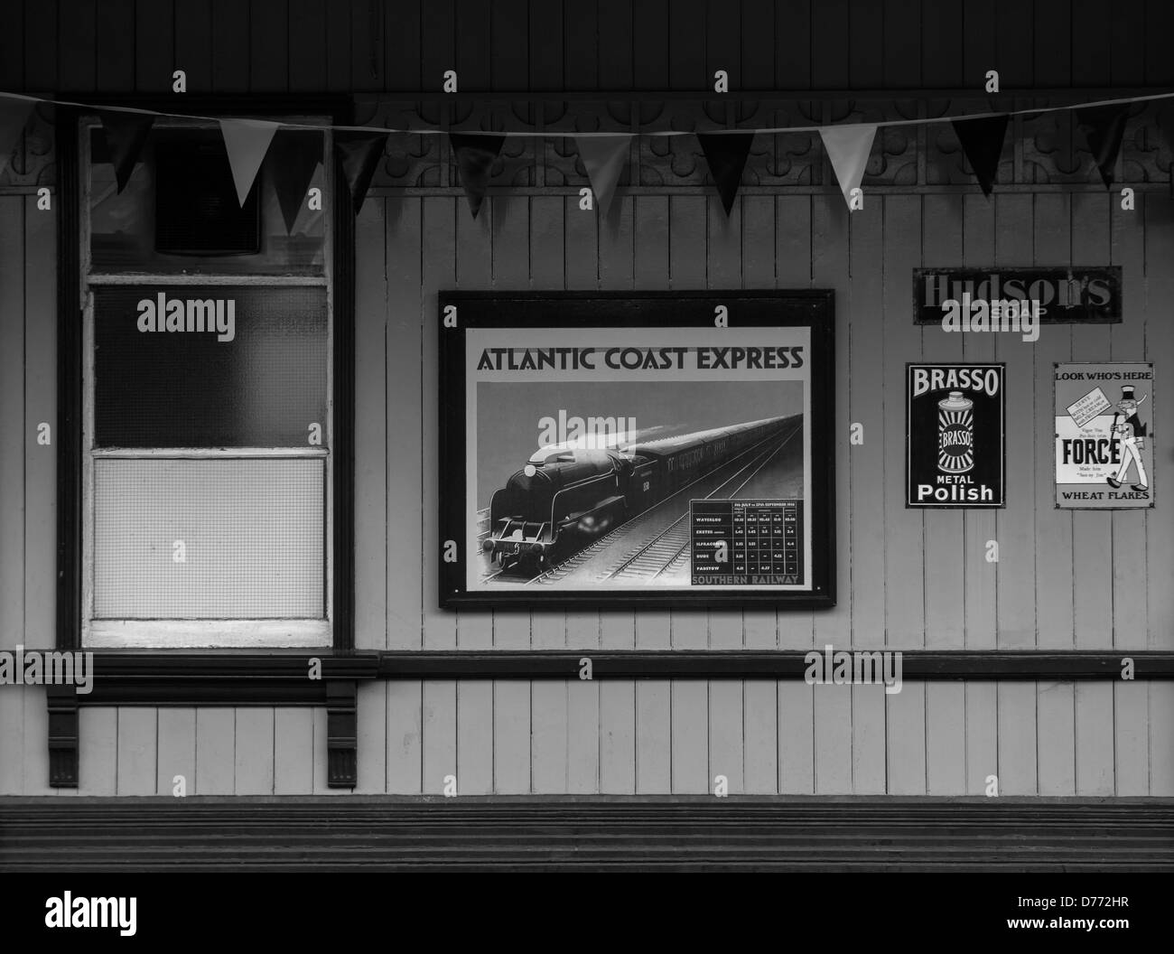 A monochrome scene of a station building on the Bluebell Railway showing adverts including the Atlantic Coast Express. - Stock Image