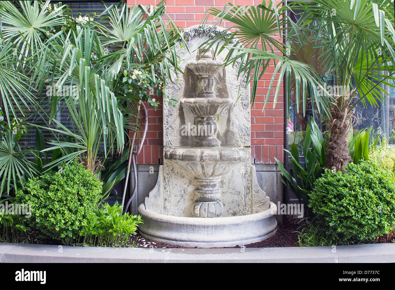 Renaissance Style Water Fountain with Cherubs and Roses in Garden Courtyard - Stock Image