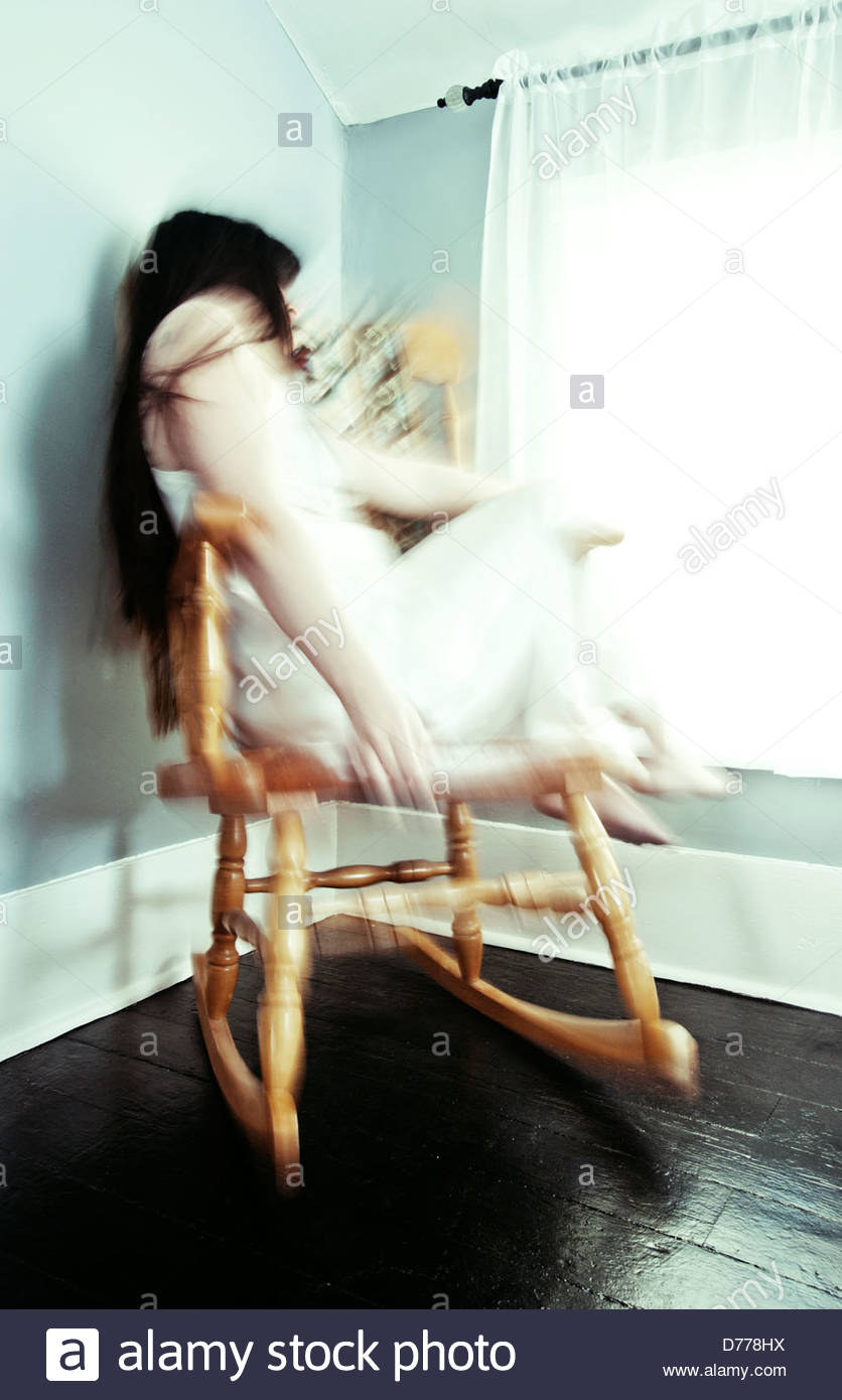 Motion blur of woman sitting in rocking chair by window in a bedroom rocking back and forth - Stock Image