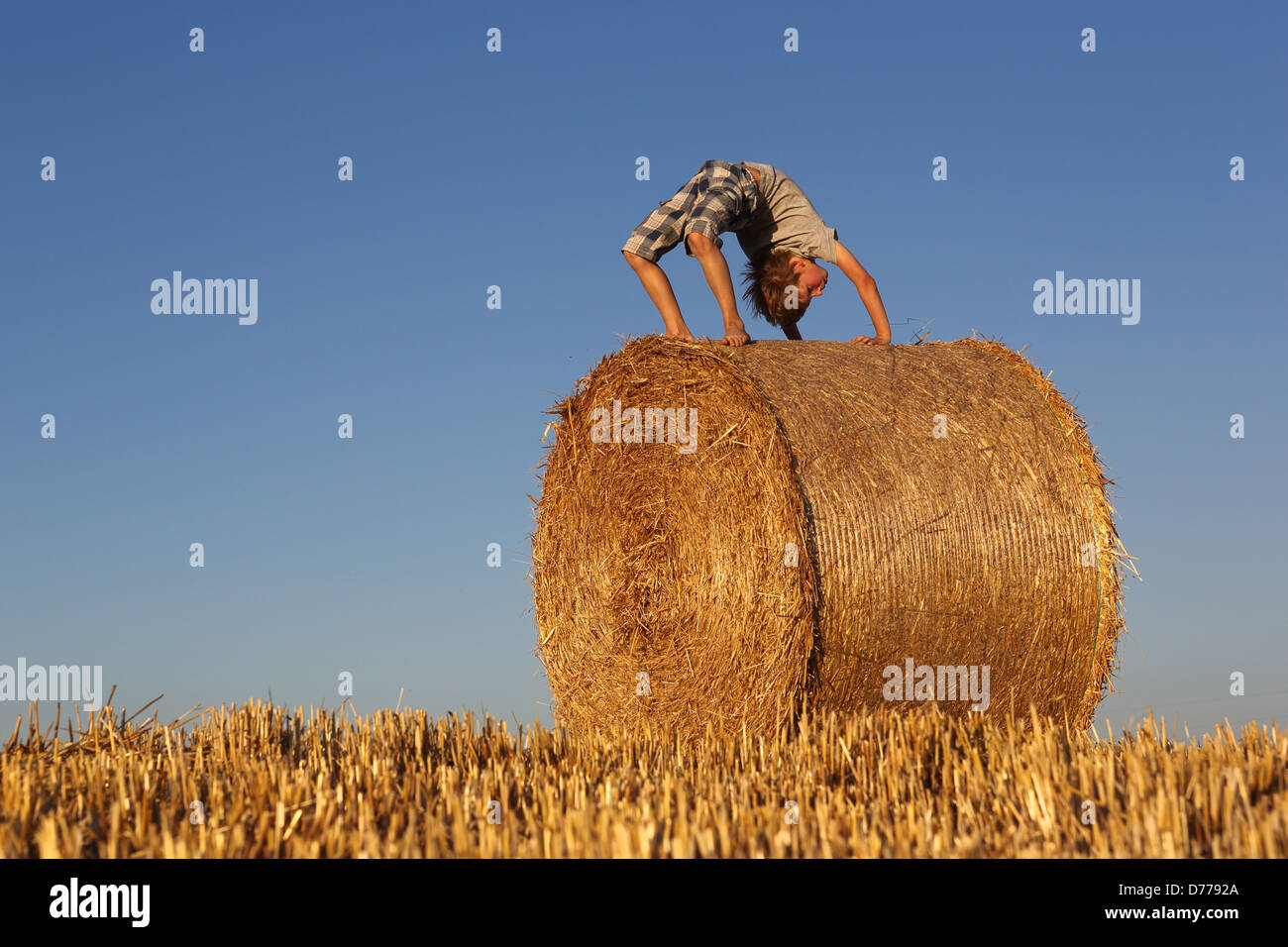 Torre Alfina, Italy, acrobatic boy bends on a straw bale - Stock Image