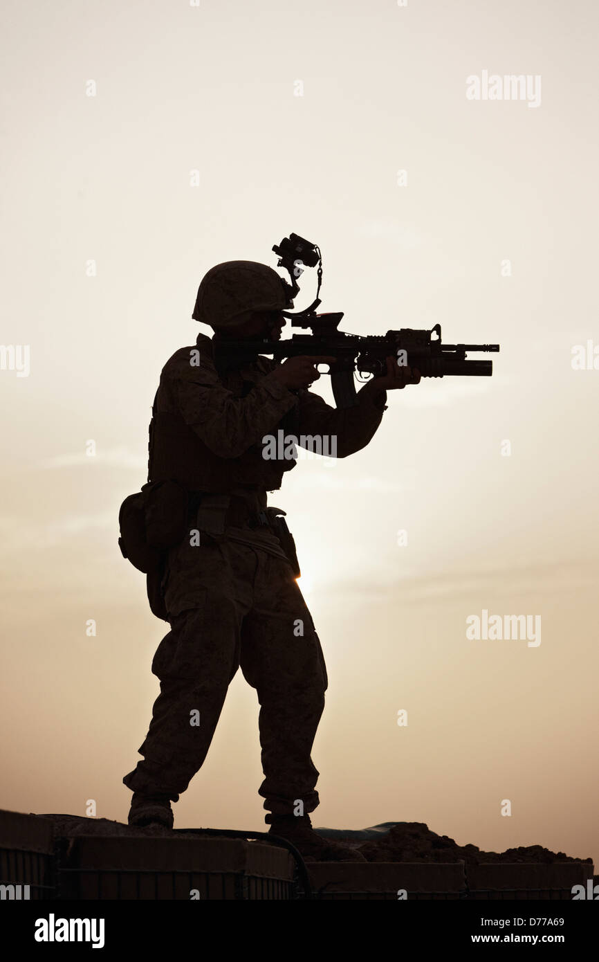 Silhouette U.S. Marine Aiming M4 Carbine During Combat Operation in Afghanistan's Helmand Province - Stock Image