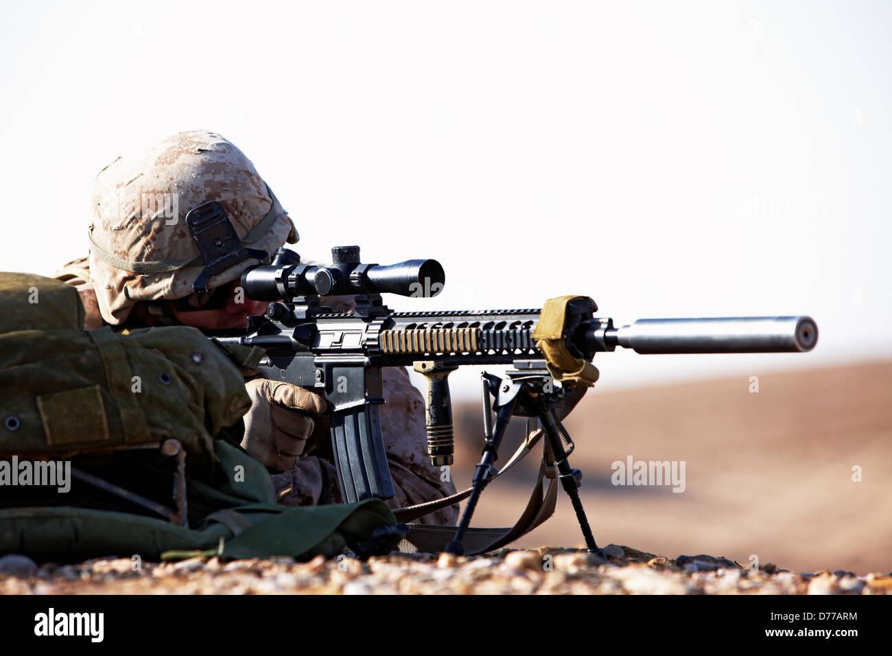 A U.S Marine Designated Marksman Peers Through Scope High Power Rifle Suppressor Mounted During Combat Operation - Stock Image