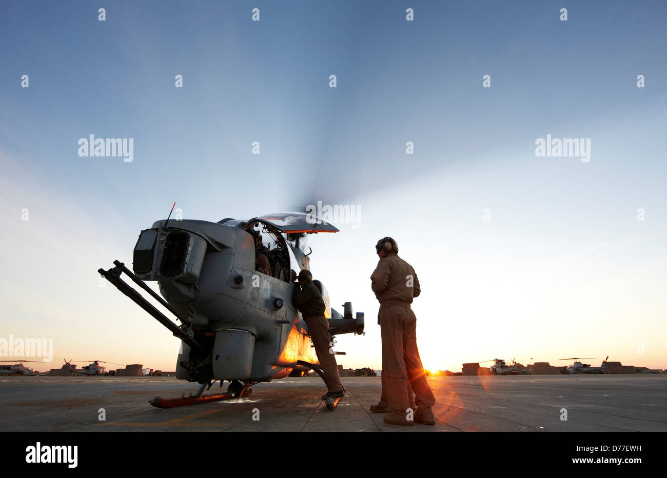 United States Marine Corps aviators ground crew prepare to launch AH-1W SuperCobra attack helicopter on combat operation - Stock Image