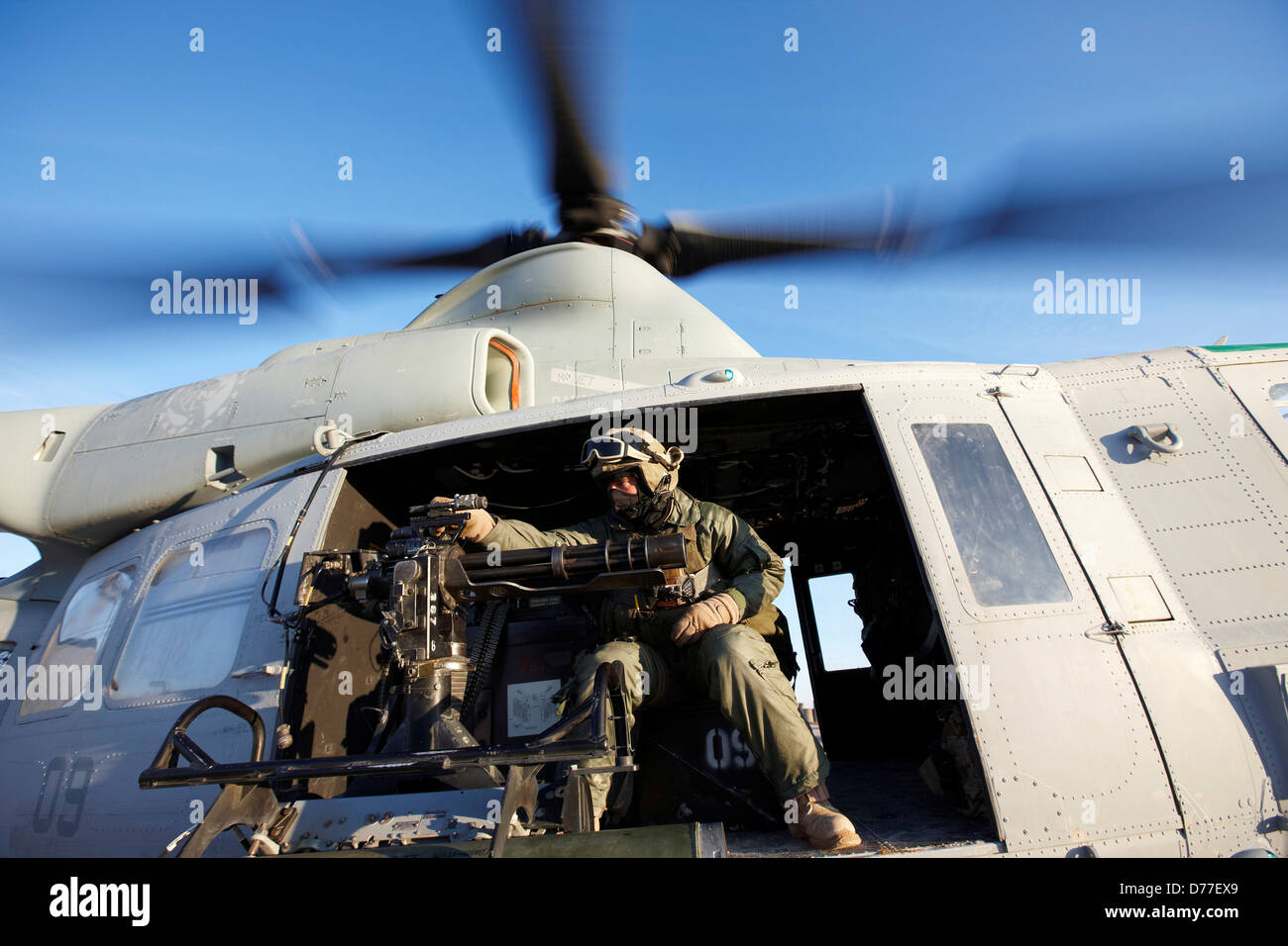 United States Marine gunner aboard UH-1Y Venom helicopter just prior to launching on combat operation in Helmand - Stock Image