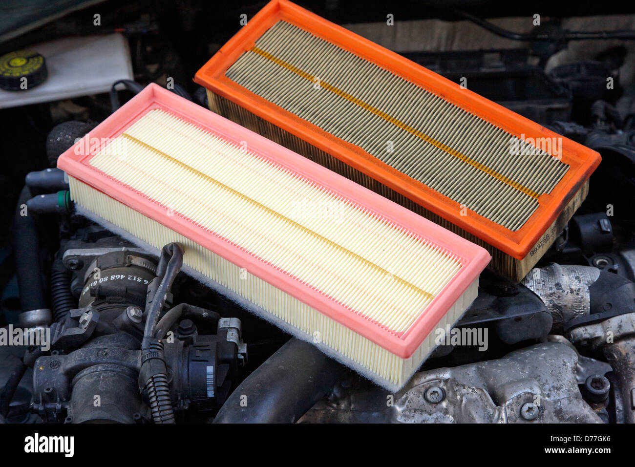 dirty air filter with replacement clean new filter in a car engine  compartment - Stock Image