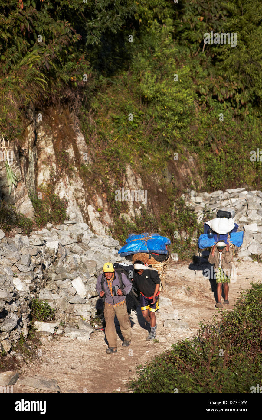 Nepal Nepalese Sherpa porters carrying backpacks - Stock Image