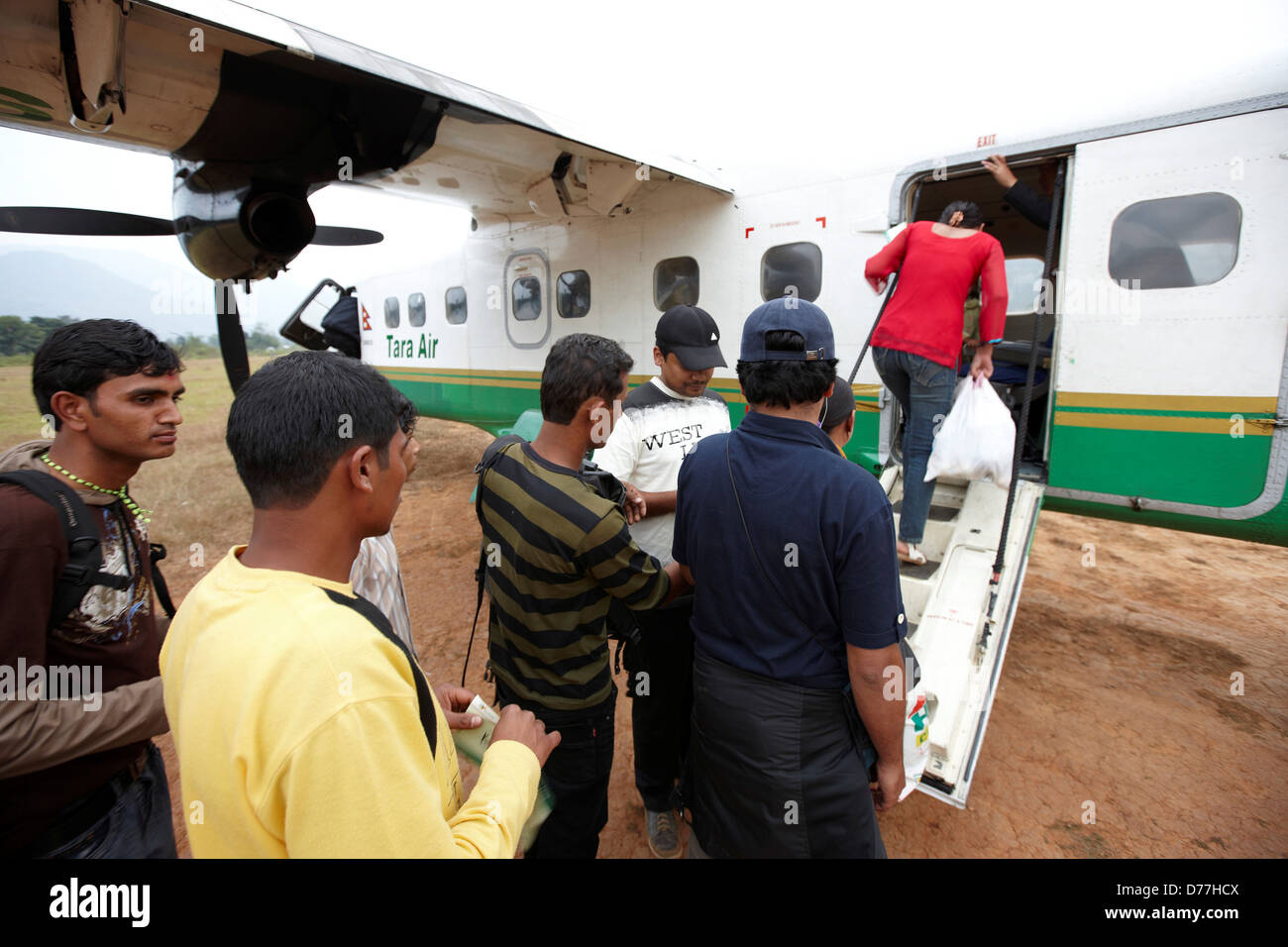 Nepal Tumlingtar passengers boarding into twin-turboprop aircraft at rural airstrip - Stock Image