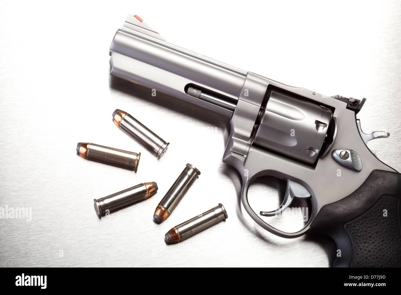 gun with bullets on steel surface - modern revolver handgun - Stock Image