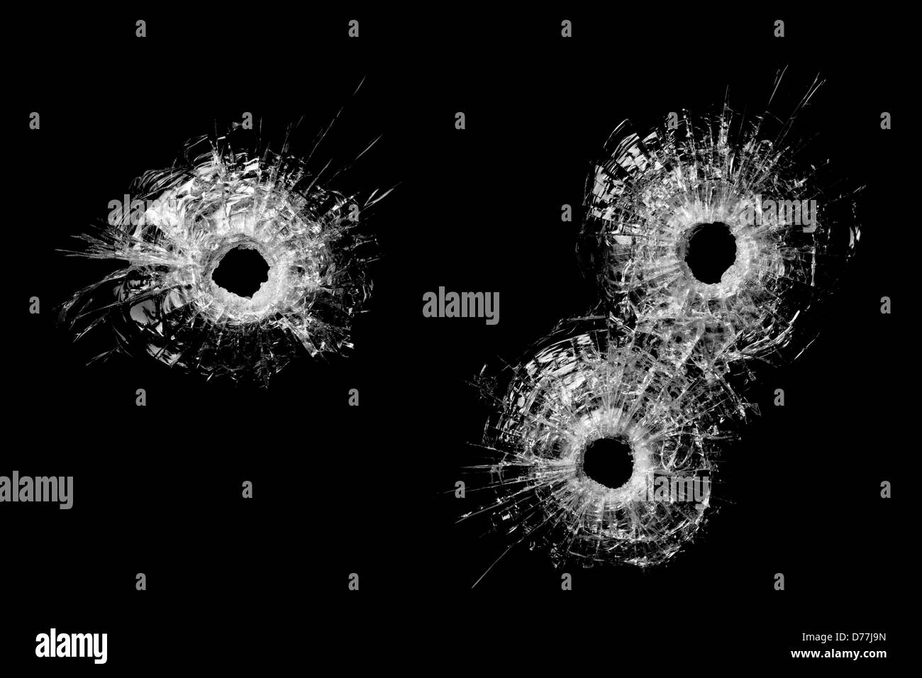bullet holes in glass isolated on black - bullet holes from .40 handgun closeup - Stock Image