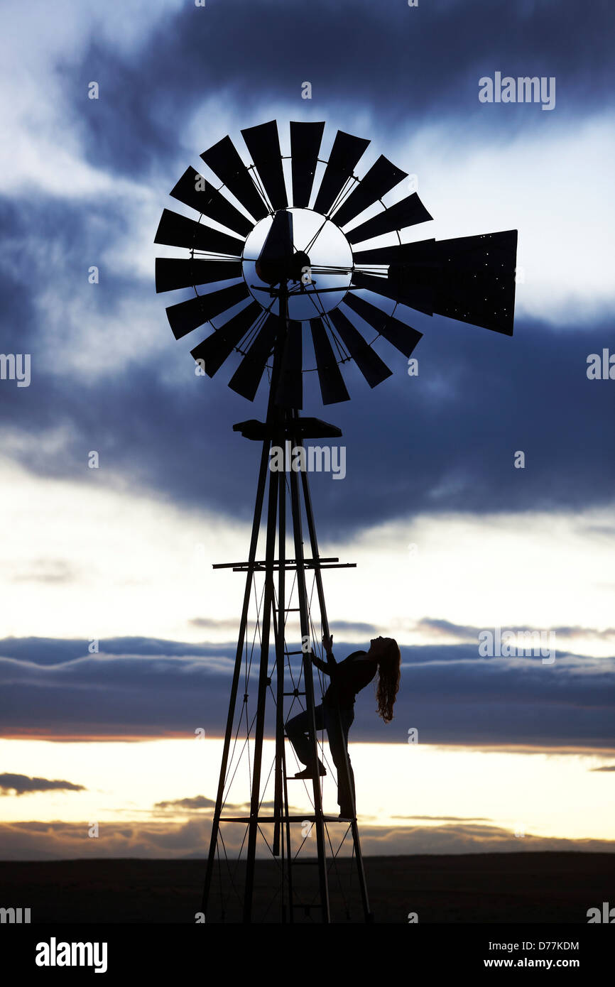 USA Colorado Silhouette woman climbing water-pumping windmill - Stock Image