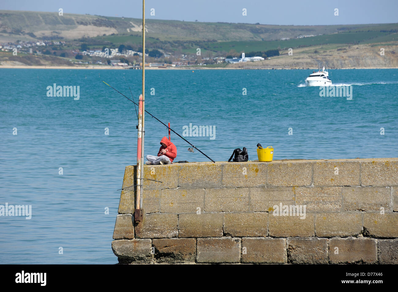 A man sea fishing from the sea wall in a red hoody weymouth dorset england uk - Stock Image