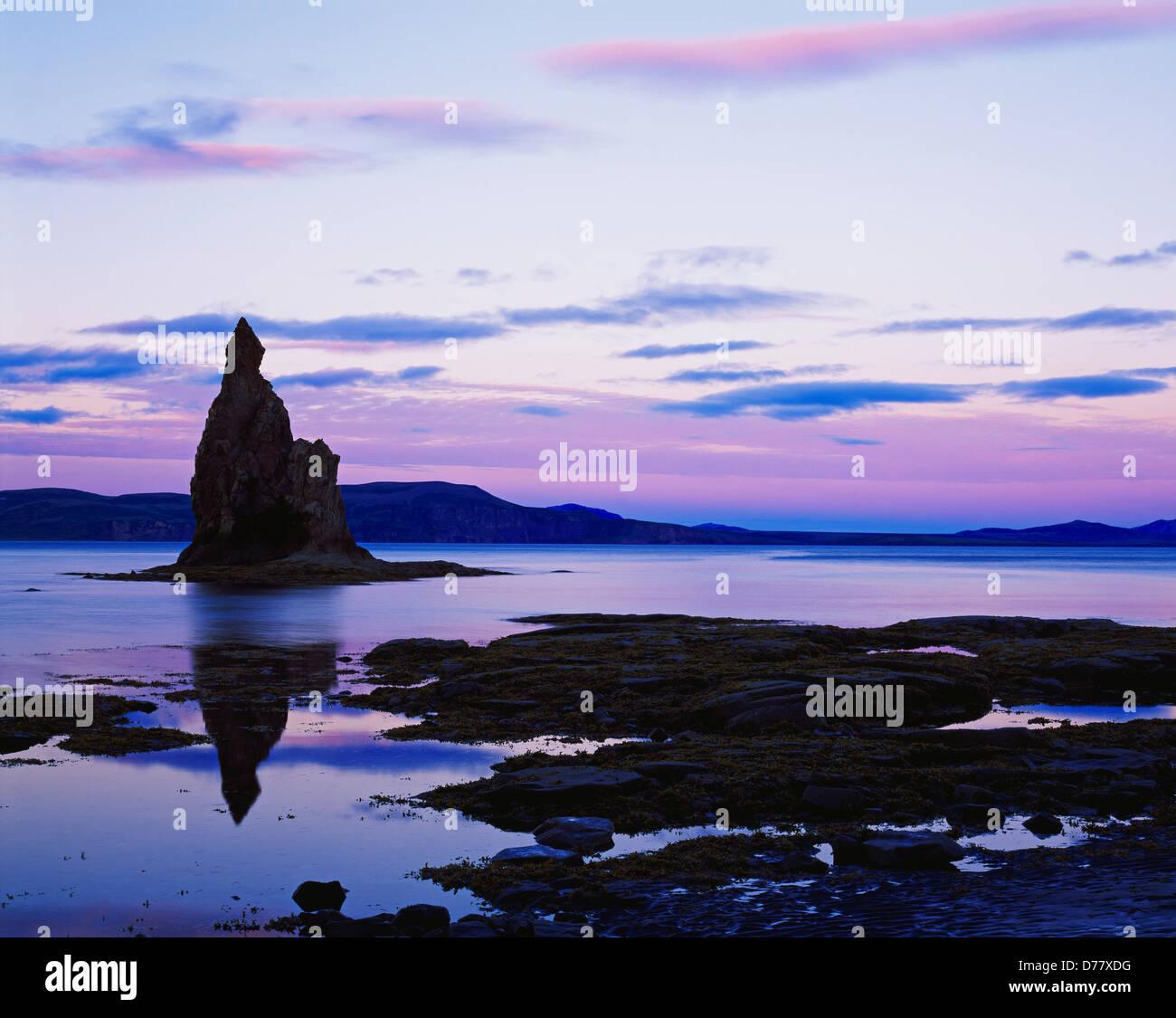 Pastel light sunset silhouetting sea stack tide pools along shore Nunavachak Bay Togiak National Wildlife Refuge Stock Photo