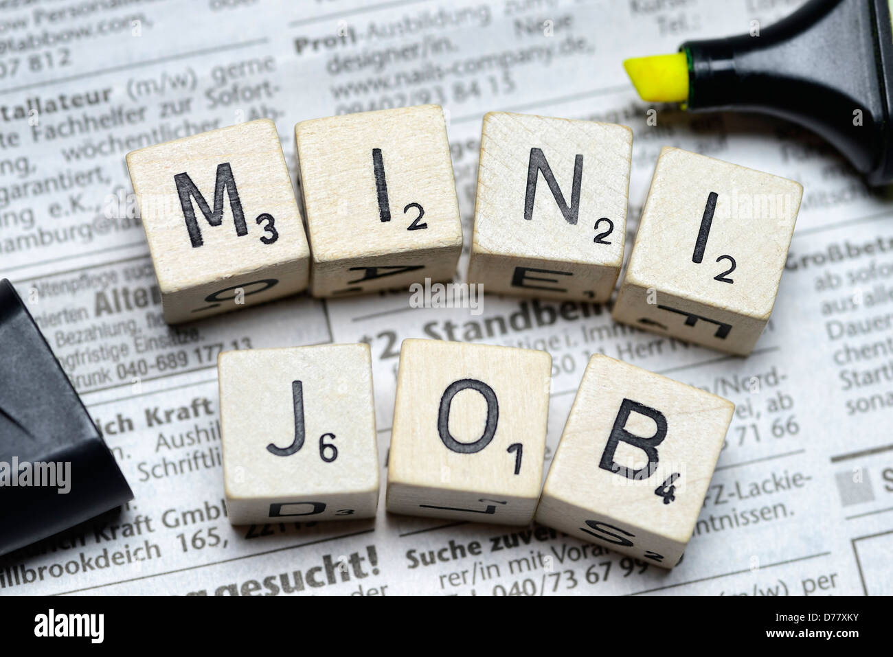 Stroke minijob from cube letter on newspaper advertisements - Stock Image