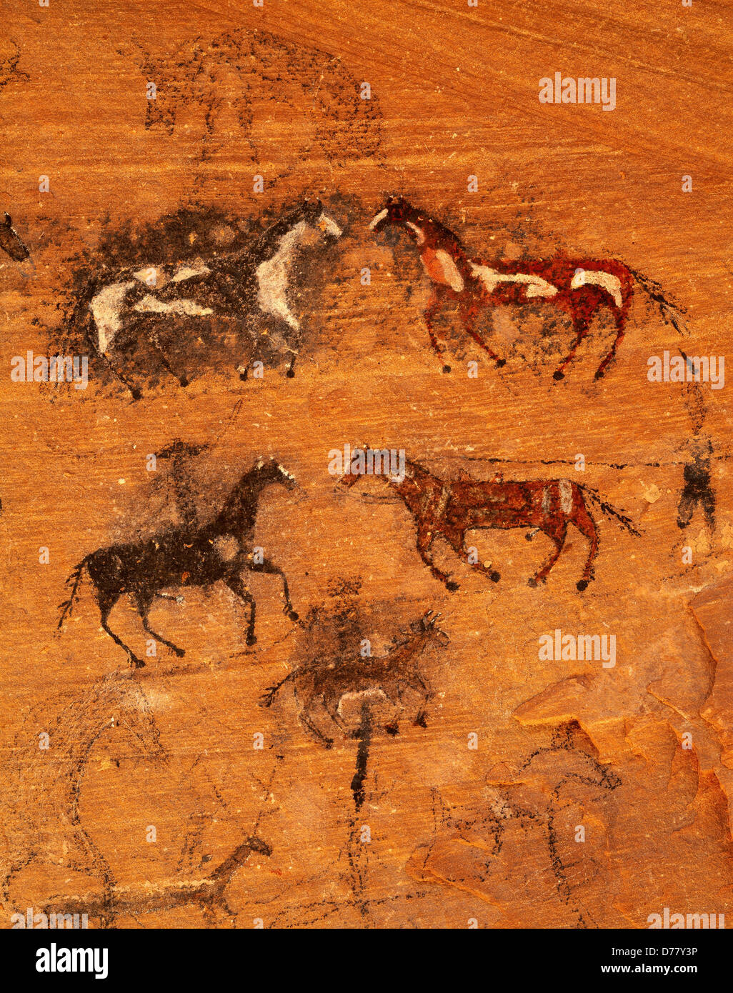 Nineteenth century Navajo pictographs horses riders other animals done in charcoal paint shallow cave in Canyon - Stock Image