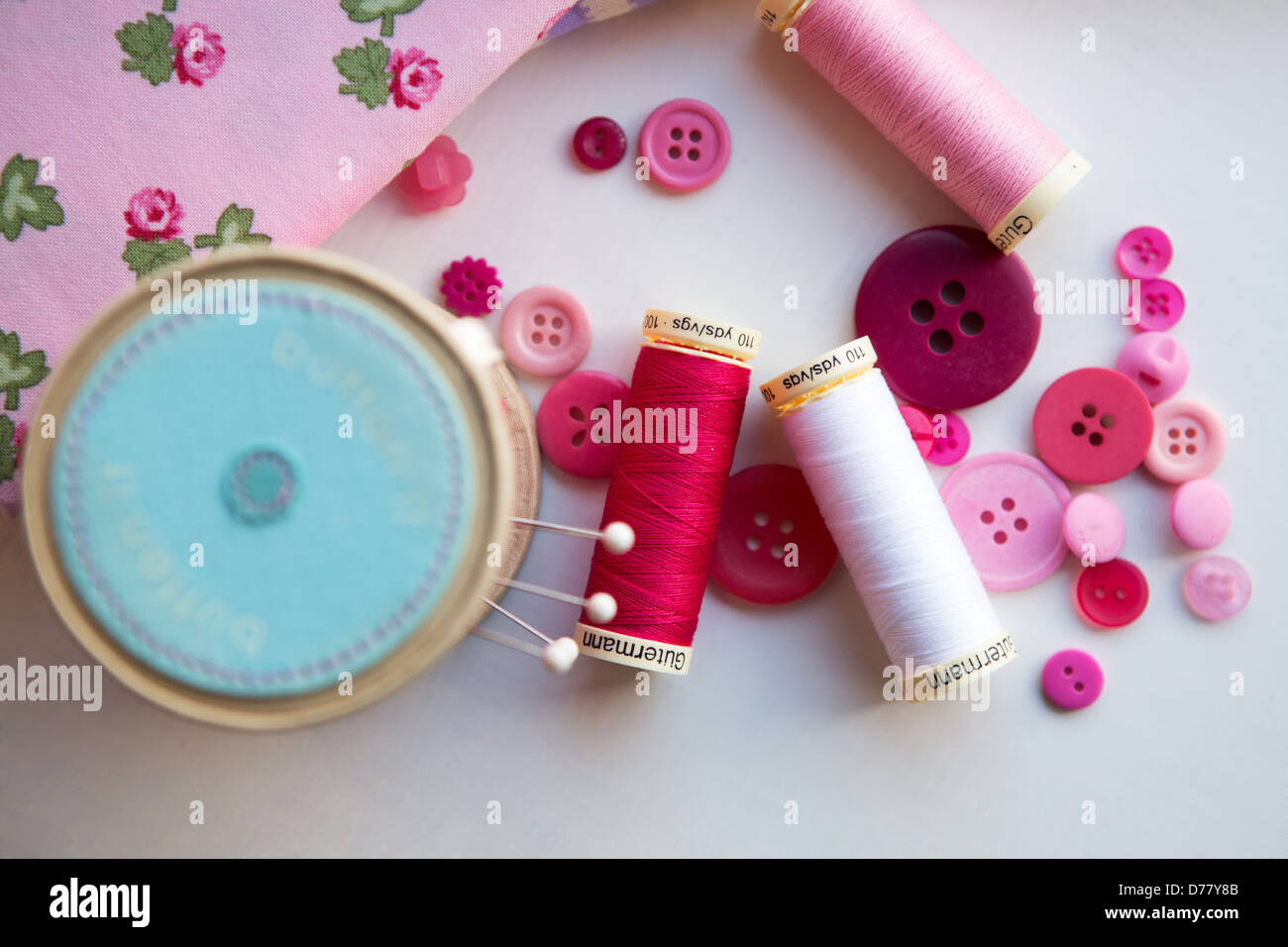 A sewing kit of thread, pins, pin cushion, fabric and