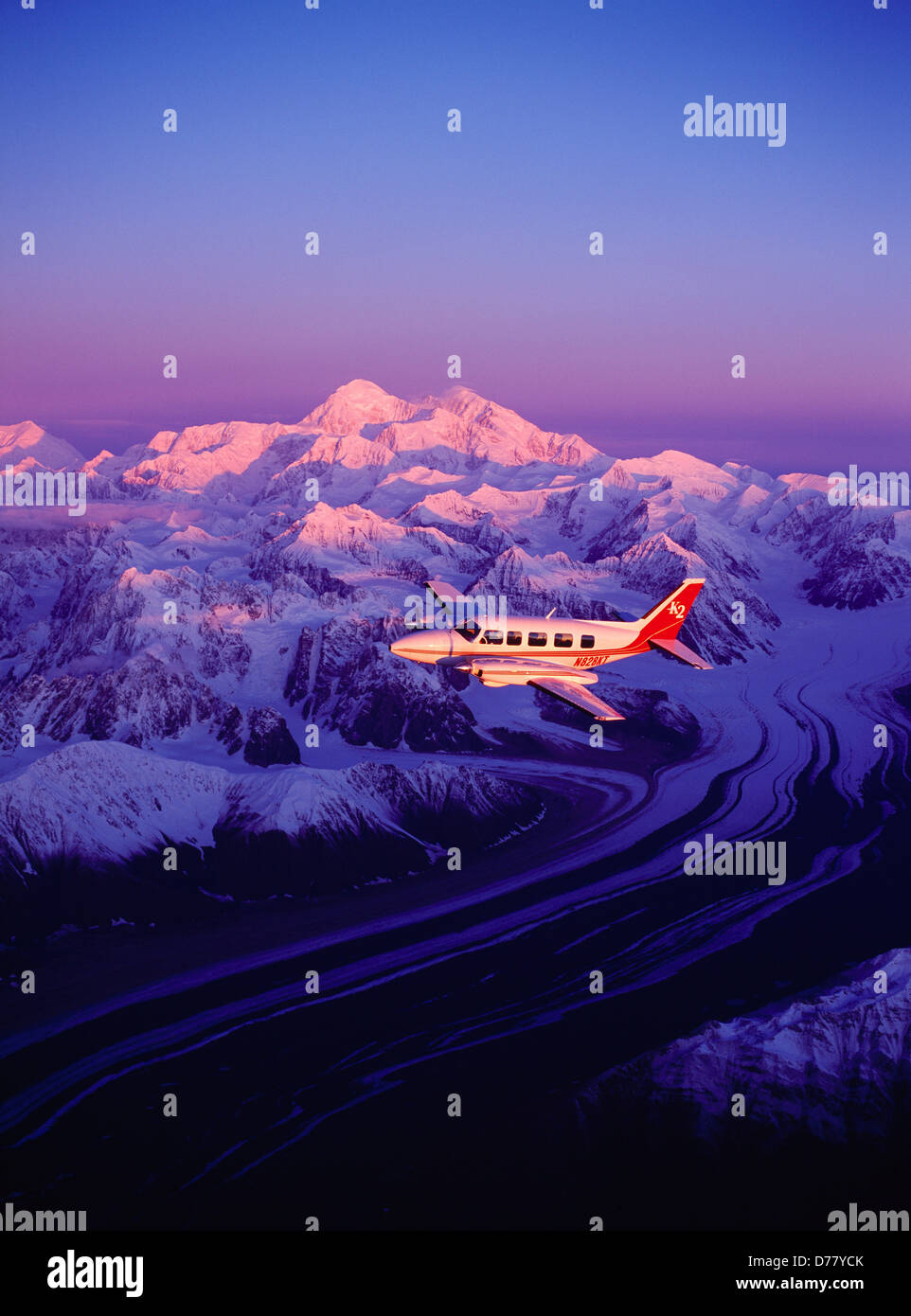 K2 Aviation's Piper Navajo Chieftain flying above Eldridge Glacier early light sunrise striking 20,320 foot - Stock Image