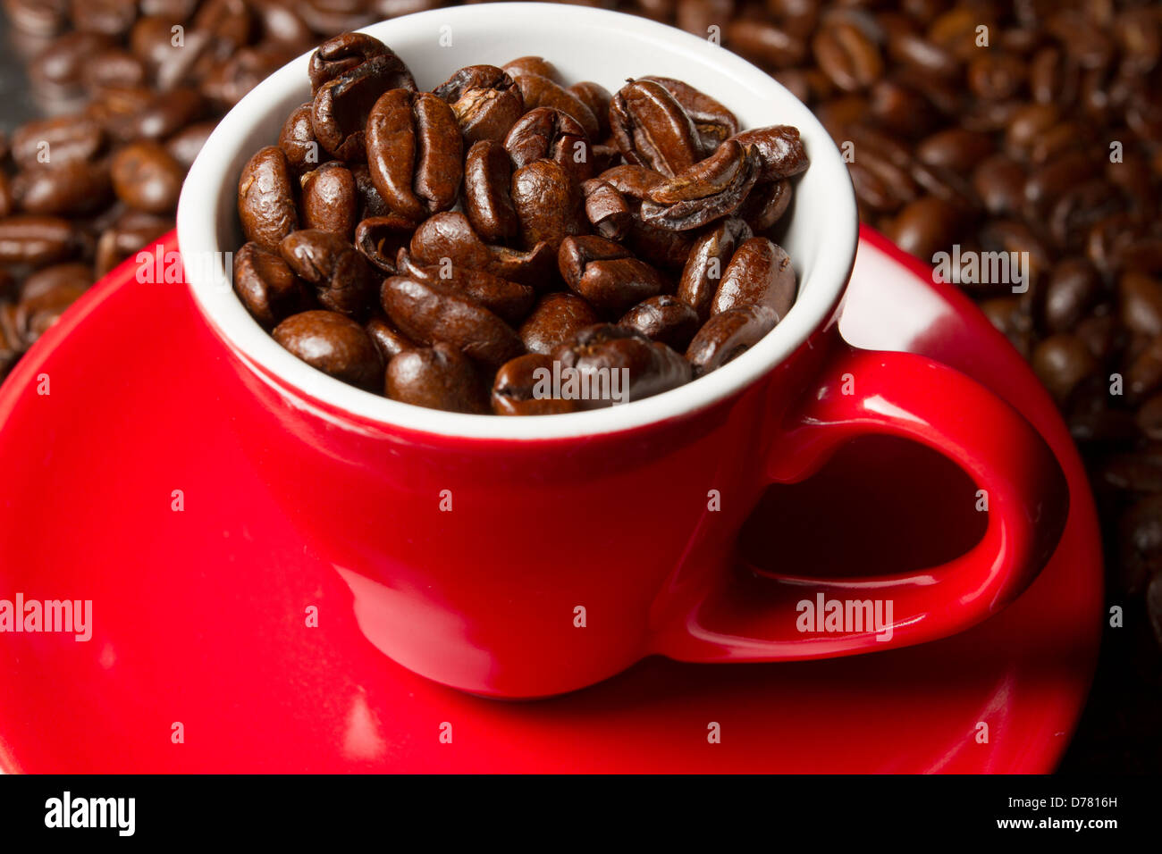 Coffee beans in a red espresso cup and saucer with fresh whole coffee beans in the background, England, UK - Stock Image