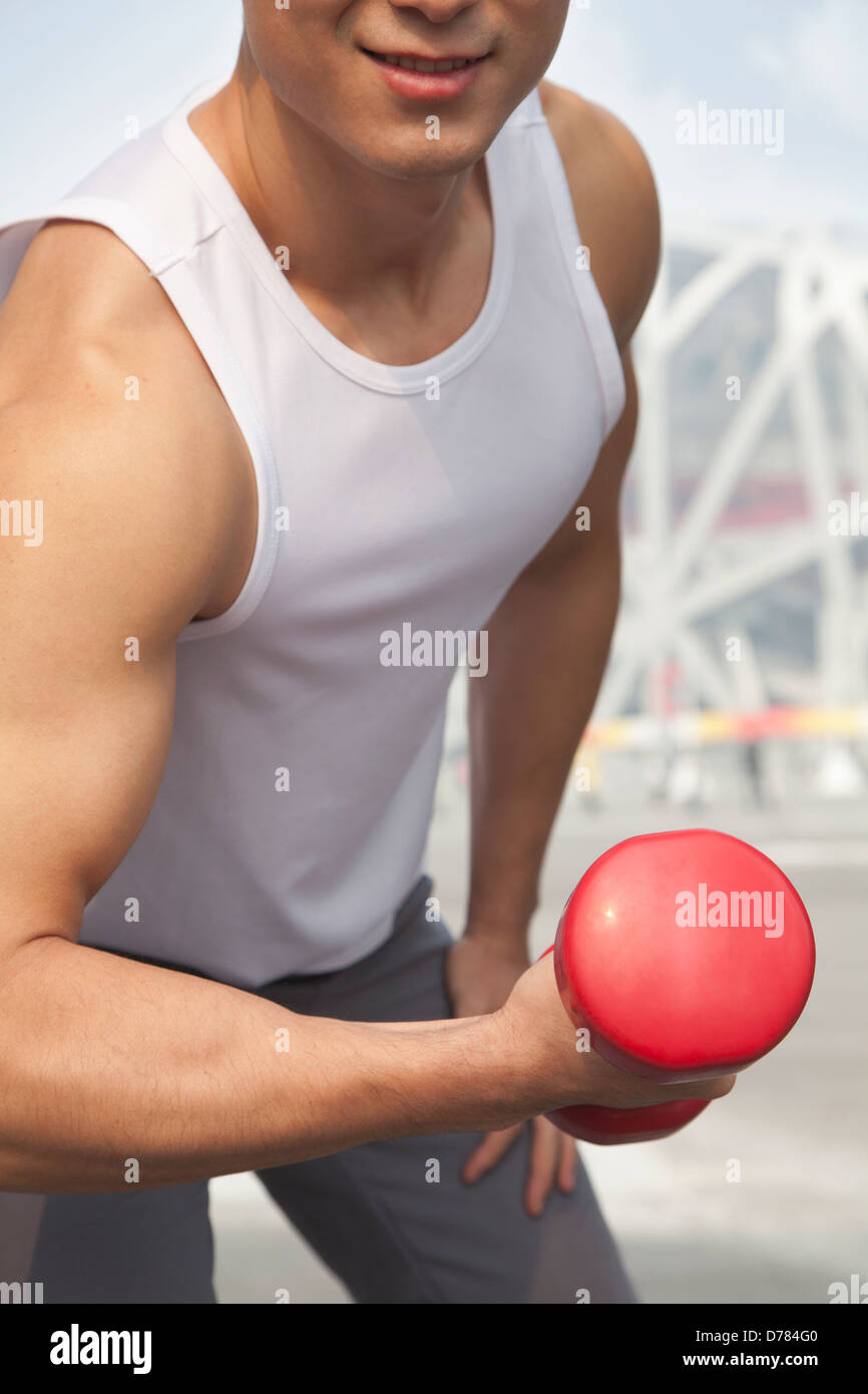 Young man exercising with dumbbell, close-up, midsection - Stock Image