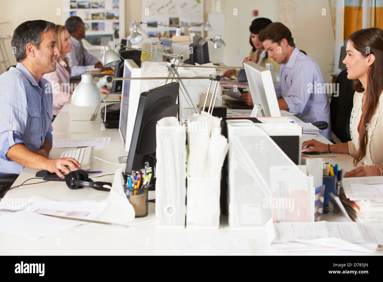 Team Working At Desks In Busy Office - Stock Image