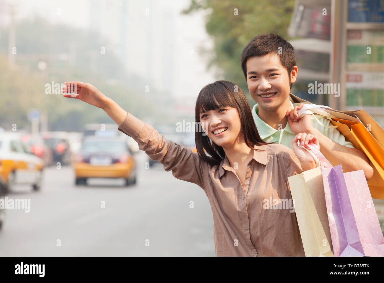 Young couple with shopping bags hailing a taxicab in Beijing - Stock Image