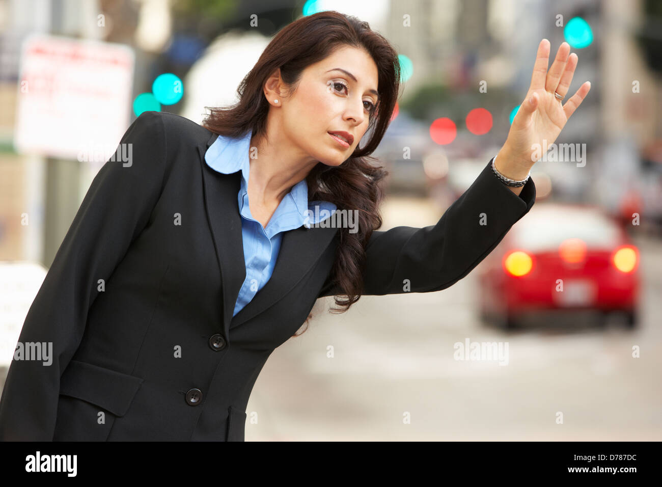 Businesswoman Hailing Taxi In Busy Street - Stock Image
