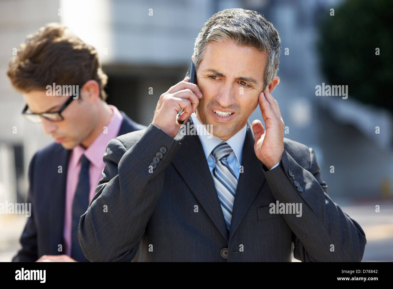 Businessman Speaking On Mobile Phone In Noisy Surroundings - Stock Image